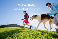 Picture of two kids, a boy and a girl, running in the park with their dog, a hound. The grass is green and the cloudless sky is blue.